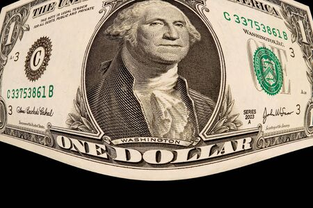 Closup view of bloated U S one dollar bill, black iso.