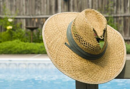 Tattered, old straw hat hanging by a swimming pool.
