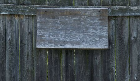 Old, warped, crusty, blank wooden signboard nailed to old wooden fence
