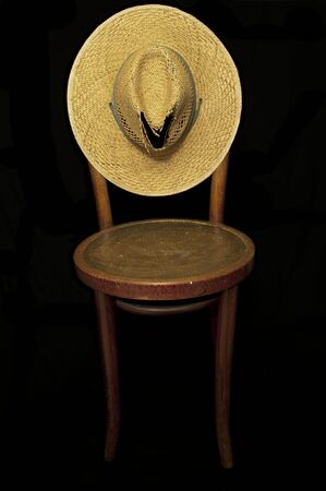 Ratty old straw hat, old armless  chair, black iso.