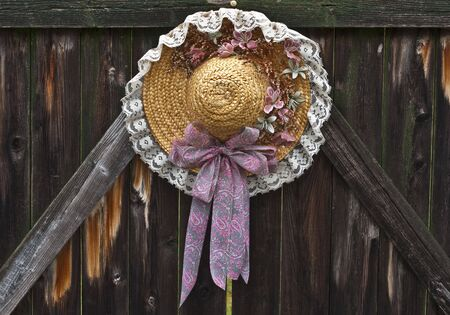 Sprng motif straw hat hanging on an old, weathered wooden gate. Reklamní fotografie