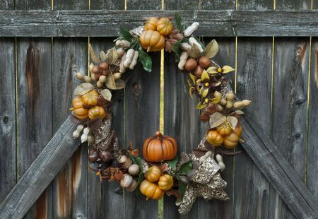 Decorative autumn wreath depicting various crops hanging on a rustic wooden fence. Reklamní fotografie