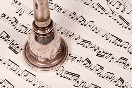 Well-worn, vintage mouthpiece atop sheet music.