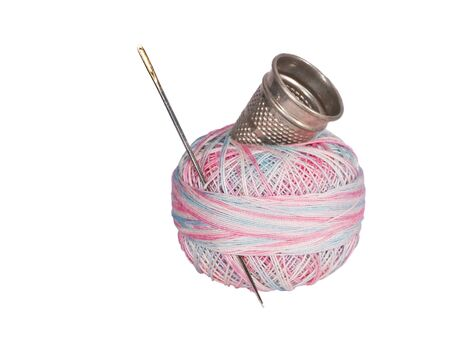 Multicolored thread with golden-eyed needle and metal thimble.