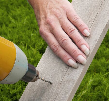 A ladys manicured hand holds a board while it is being drilled.