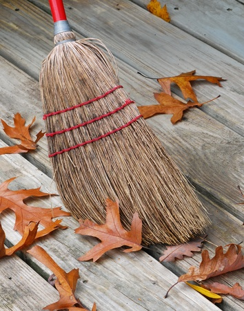 Old-fashioned jackstraw broom head  surrounded by oak leafs. Reklamní fotografie