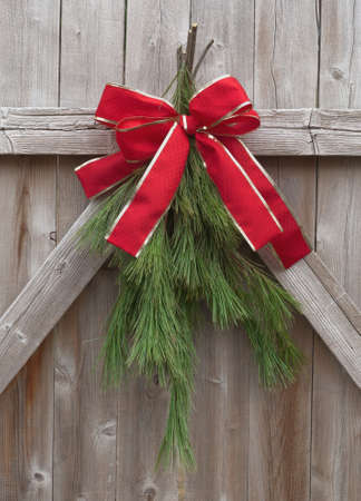 Christmas greens tied with red ribbon on a rustic wood fence.