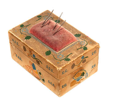 Old cardboard sewing needle box with built-in pincushion, white isolation.