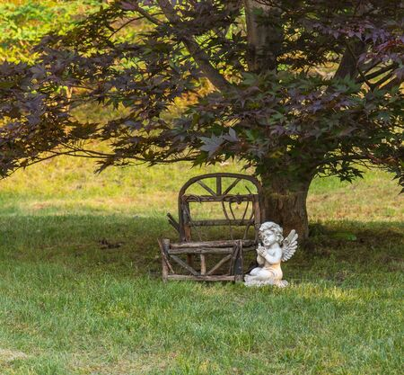 Miniature outdoor wooden bench, angel sitting along side.
