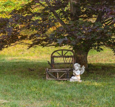 Miniature outdoor wooden bench, angel sitting along side. Reklamní fotografie - 13795068
