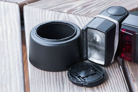 Camera lens hood, lens cap, and flash gun