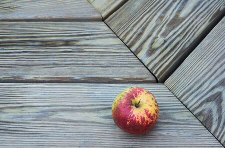 Closup view of a small apple on a wooden bench or table.