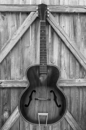 Vintage akoestische gitaar opknoping op een oude, kromme, verweerde hek, monochroom.