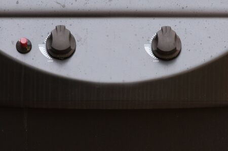 Closeup view of gas grill controls, with dials and a button. Reklamní fotografie