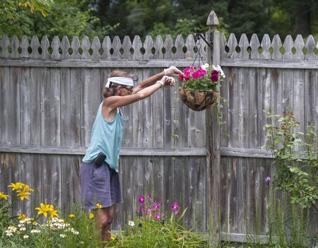 Middle aged woman trims flowers hanging in a basket in her garden