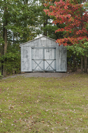 View of rural shed in early autumn, with red foliage and fallen leaves on the lawn