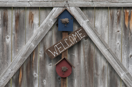 Rustic  welcome  sign displayed on a weathered wooden fence gate  Reklamní fotografie