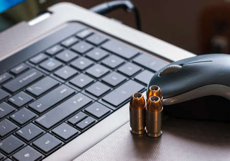Closup of laptop computer, mouse, and gun bullets, representing the concept of cyber attacks
