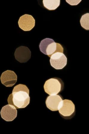 Random pattern of nonagonal light sources on a black background.