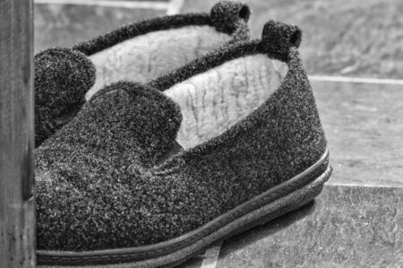 Close-up monochrome view of mens fuzzy slippers on a slate floor..
