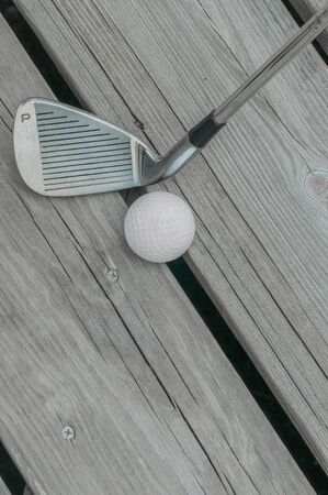 Well-used golf club pitching wedge (marked P) and golf ball on a weathered wooden deck.