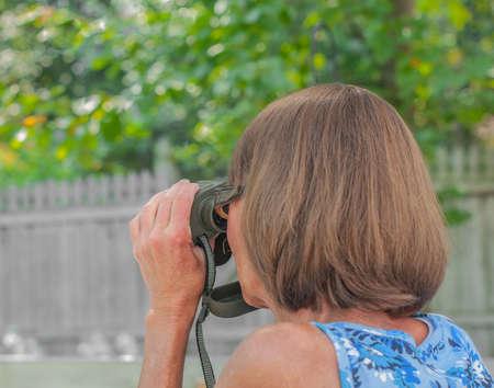 Woman looks through binoculars, side-rear view, exterior summer shot, narrow depth of field, focus on eyeglass frame... Reklamní fotografie