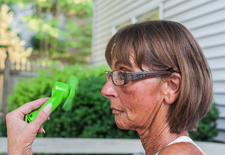 Senior woman cools herself with a handheld portable battery operated personal fan. Outdoor setting.