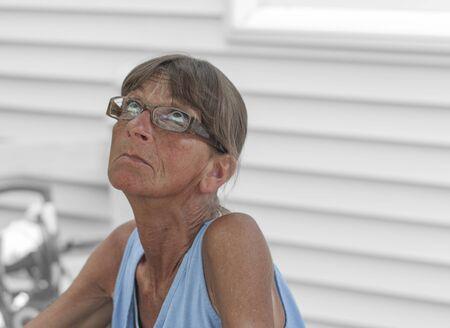 Middle-ages female gazes skyward, exterior warm weather, summertime shot.