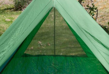 Looking  through a backpacking tent window through the length of the tent past the open door to ground outside. Tent is 40 years old, showing peeling waterproofing and general age. Reklamní fotografie - 57696253