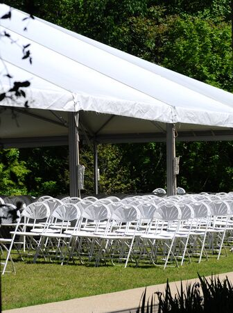 View of outdoor event seating, featuring white folding chairs under a white canopy, on a sunny day. Reklamní fotografie - 58949938