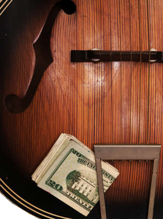 Detail view of old, beat-up acoustic guitar, with a wad of U.S. paper money stuck in the tailpoece. Reklamní fotografie