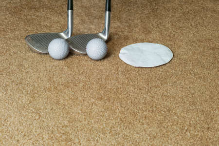 Two golf club wedges, two golf balls, and paper cut-out representing putting cup on an indoor carpet. Reklamní fotografie - 92841798