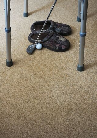 View of camoflage bedroom slippers, golf ball, golf club, and legs of a disabled persons walker against a neutral color carpet background.