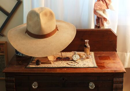 Cowboy hat displayed on a hat stand, with 100+ year-old medicine bottles and an old pocket watch, all displayed on a late 19th century wash stand with crystal drawer pull knobs.