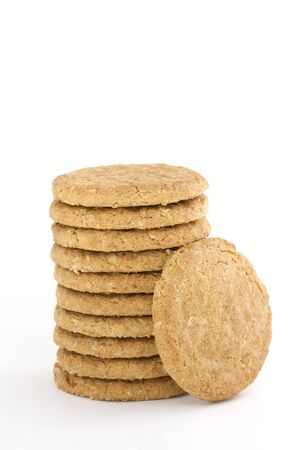 leant: Pile of nine oaty cookies with one leant against isolated on white