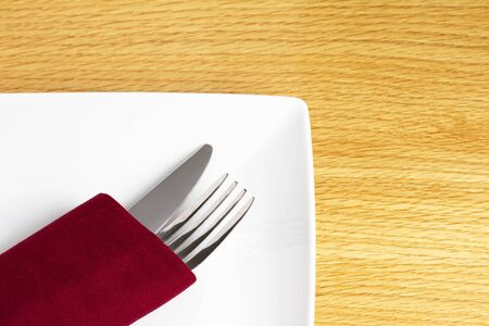 Knife and fork in red napkin on plate photo