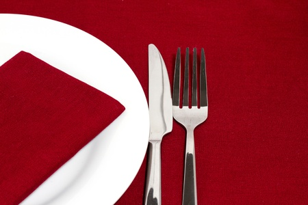 Knife and fork with white plate on red tablecloth photo