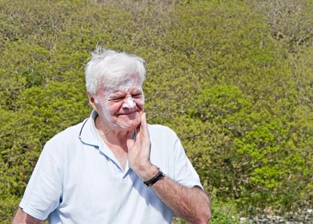 grey haired: Senior grey haired  man putting on suntan cream
