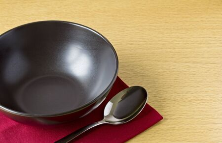 Black bowl with spoon on table with red napkin Stock Photo - 10854868