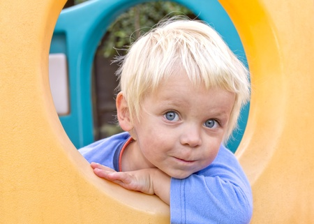 Cute blond boy playing in  climbing frame photo