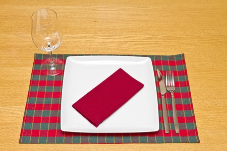knife and fork with glass on green and red tablecloth with white plate photo