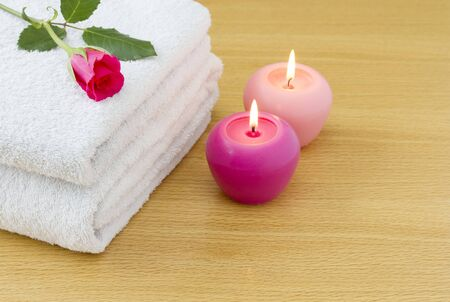 White towels with pink candles and red rose spa concept photo