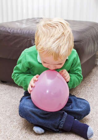 blow up: Blond toddler boy trying to blow up a pink balloon
