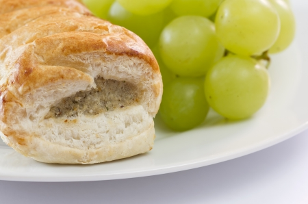 Sausage roll and grapes on a plate photo