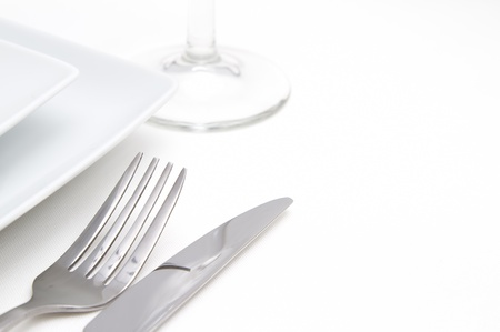 Dinner place setting  white square china plates with silver cutlery and glass