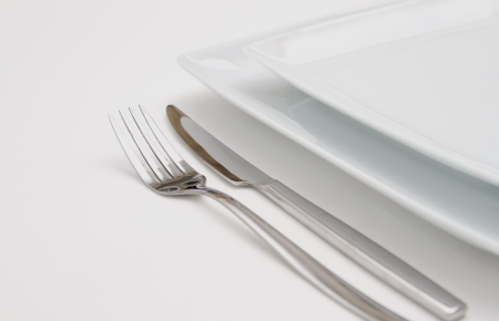 Dinner place setting  white  plates with silver fork and knife photo