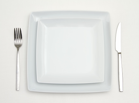 Dinner place setting  white square china plates with silver fork and knife