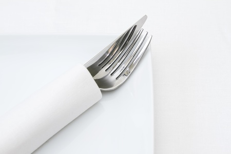 Place setting, knife and fork in white napkin Stock Photo