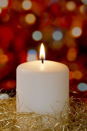 Cream candle with gold tinsel and blurred light background photo