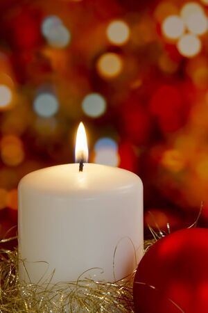 Cream candle with gold tinsel, bauble and blurred light background photo